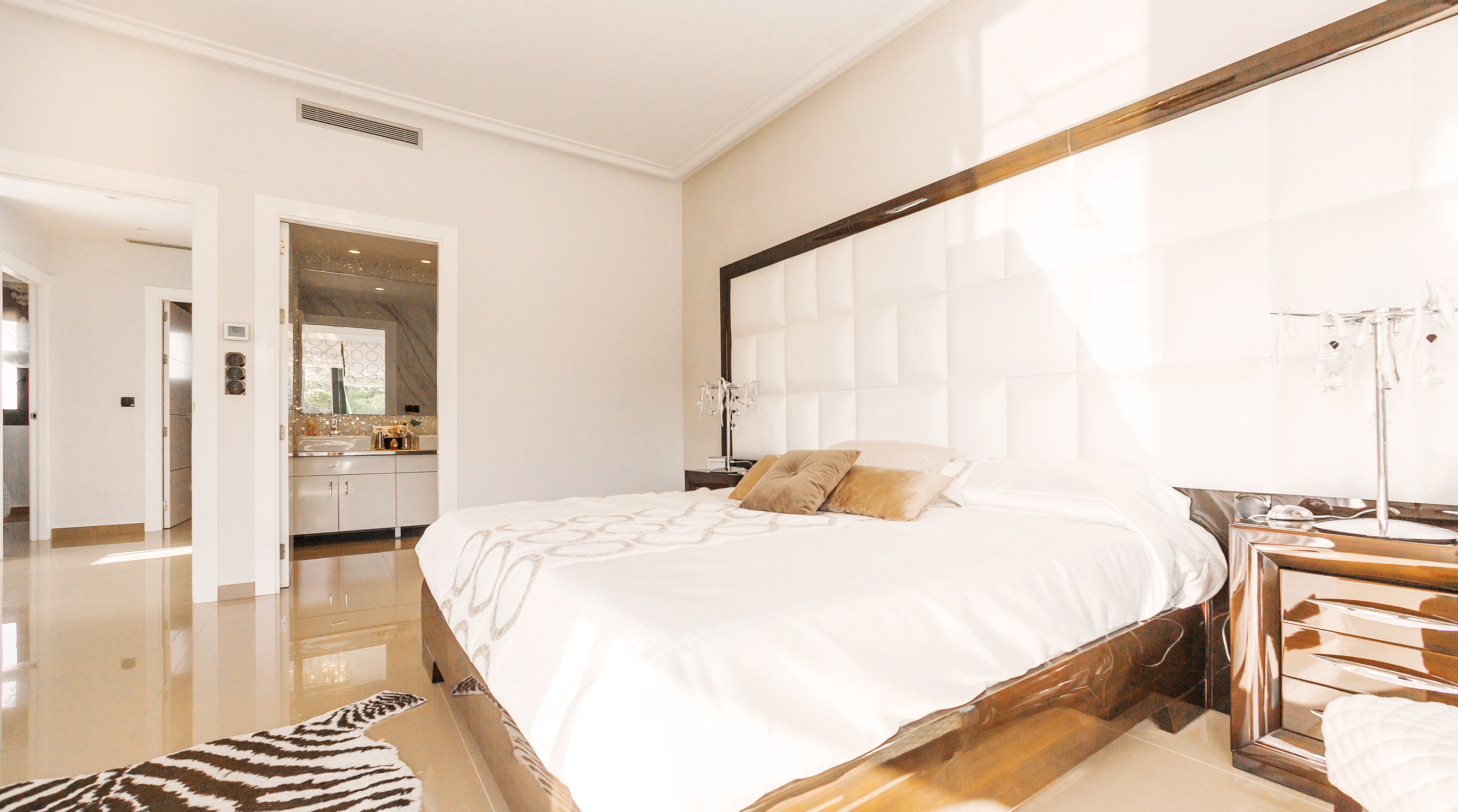 Large bed with white comforter in room