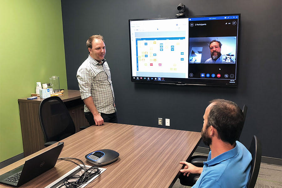 Two men speaking in a conference room.